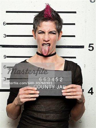 Studio mugshot of mature woman sticking out tongue
