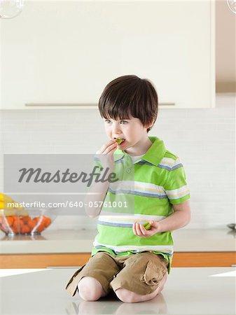 USA, Utah, Boy (4-5) Essen Kiwi in Küche
