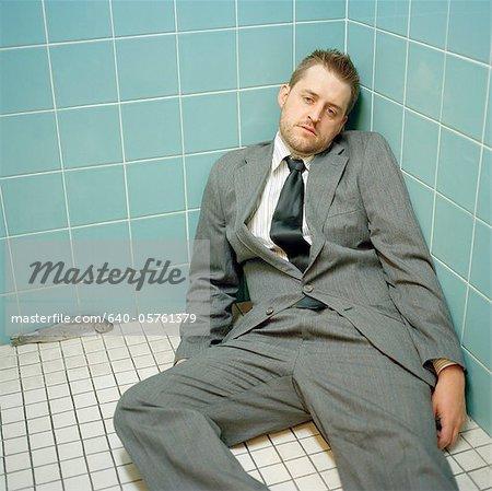 USA, Utah, Salt Lake City, Mid adult man wearing suit lying down at corner