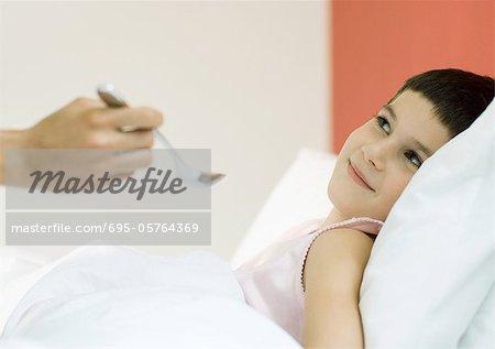 Kind im Bett, gefüttert mit Löffel