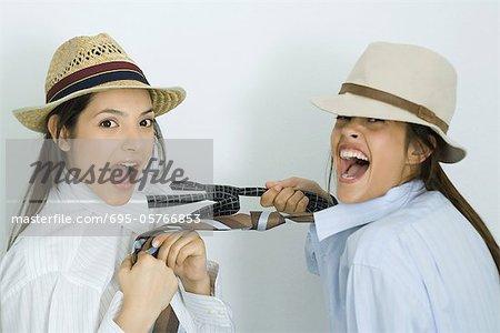 Deux jeunes amis vêtus de chapeaux, tirant leurs cravates, riant de caméra