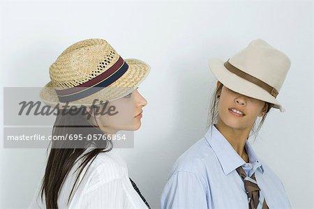 Deux jeunes amis femelles portant des chapeaux et cravates, regardant les uns les autres, les yeux couverts