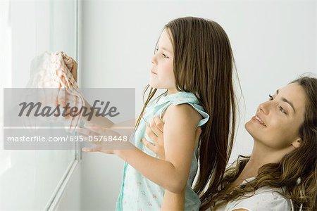 Reinigung der Fenster, Mutter hält ihr beide lächelnd mädchen