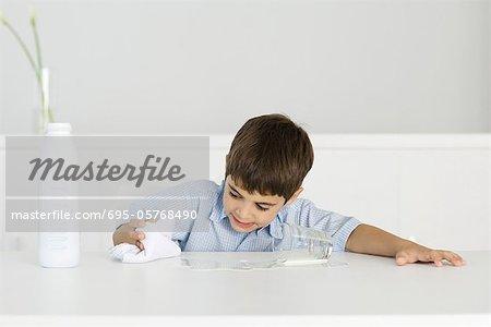 Junge verschüttete Milch mit Tuch abwischen