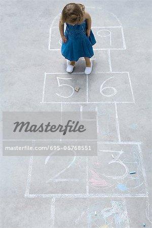 Kleines Mädchen Hopscotch Startaufstellung stehen, blickte auf Rock, hohen Winkel anzeigen