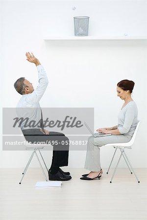 Profis sitzen von Angesicht zu Angesicht Mann wirft Papierkugel in Papierkorb, Frau mit laptop