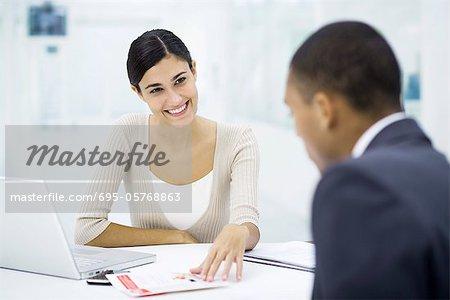 Professionnelle femme assise avec le client au bureau d'examiner la brochure