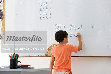 Étudiant de l'école primaire travaille des équations mathématiques sur tableau blanc