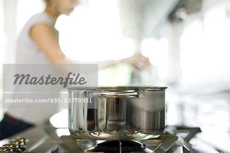 Topf Kochen am Herd, Frau im Hintergrund