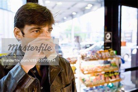 Homme de boire du café dans les magasins de proximité