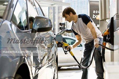 Man refueling vehicle at gas station