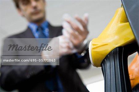 Man putting putting on disposable gloves preparing to refuel vehicle