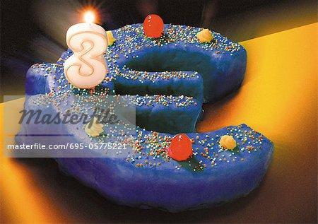 Gâteau d'anniversaire signe euro, bougie de trois nombres brûlant sur le dessus.
