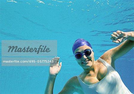 Woman smiling underwater, underwater view.