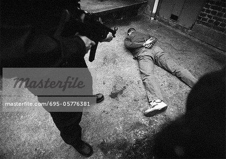 Homme debout et pointant vers le pistolet mitrailleur à homme face contre terre sur le sol, b&w