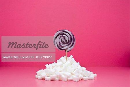 Concept de restauration, sucette qui sort des tas de morceaux de sucre