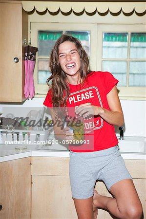 Femme, manger des cornichons en cuisine