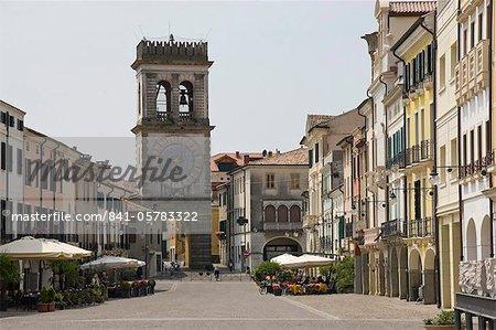 Cafés de la rue et la porte de la ville avec la tour de l'horloge ornementale, Este, Vénétie, Italie, Europe