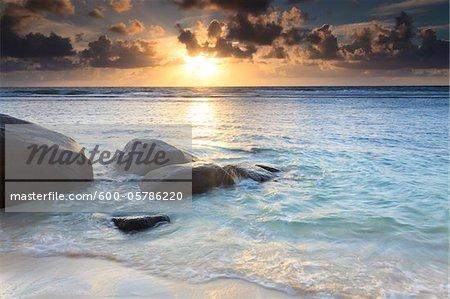 Felsen am Strand bei Sonnenaufgang, Anse Parnel, Mahé, Seychellen