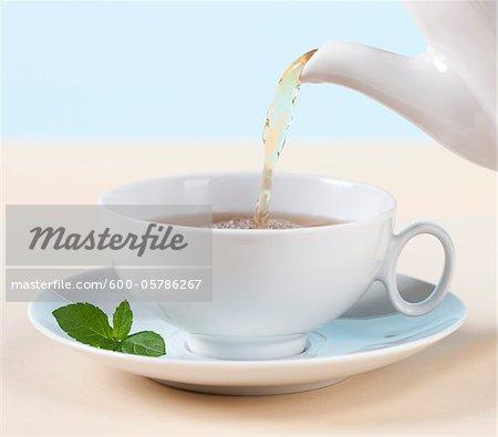 Nahaufnahme von Tee in Tasse aus Teekanne gegossen