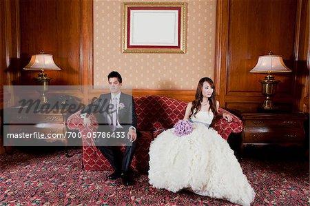 Mariée et le marié assis sur la causeuse