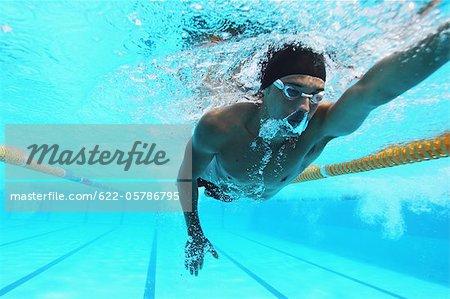 Homme nage dans la piscine, sous l'eau