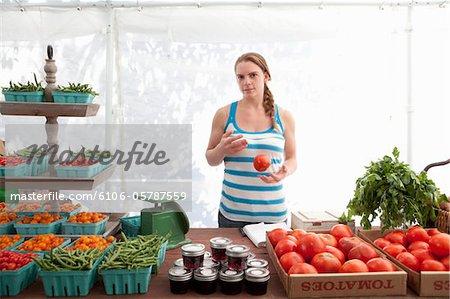 Jeune agricoles stand propriétaire lancers tomate