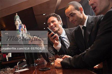 Drei Geschäftsleute immer Getränke an der bar