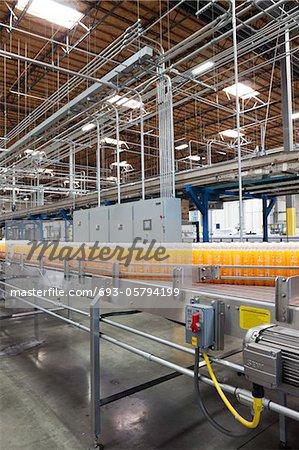 Orange juice bottles on conveyor in bottling plant