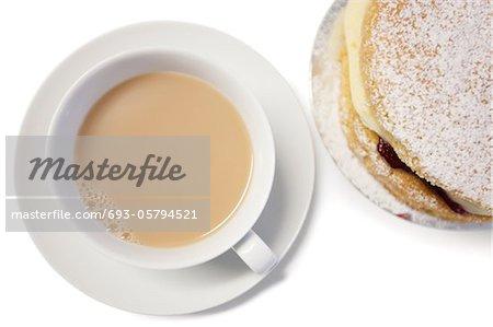 Erhöhte Ansicht der Teetasse und Puderzucker Kuchen slice