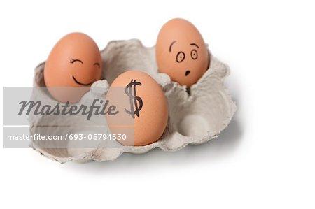 Drei Eier im Karton mit einem Dollar-Zeichen auf einem Ei