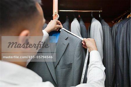 Tailor measuring shoulder of the suit