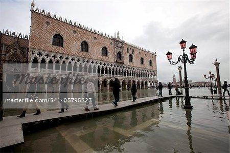 Touristes marchant sur les passerelles pendant la marée haute à la place Saint-Marc, Palais des Doges dans le fond, Venise, UNESCO World Heritage Site, Veneto, Italie, Europe