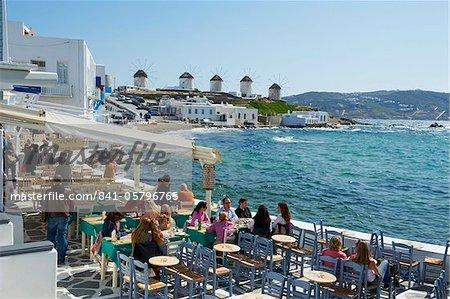 Café bar sur le bord de la mer avec les cinq moulins à vent (Kato Mili) au-delà, petite Venise, la ville de Mykonos, Chora, île de Mykonos, Cyclades, îles grecques, Grèce, Europe