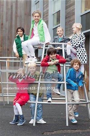 Porträt von Schulkindern auf Jungle Gym in der Schule
