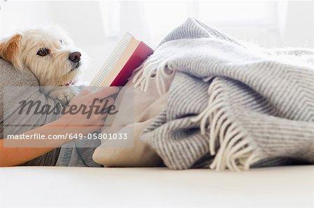 Frau mit Hund im Bett lesen