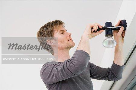 Man installing light fixture in house