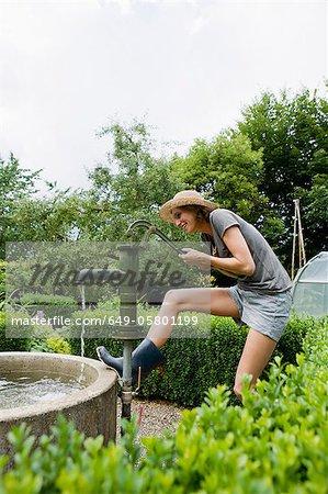 Sourire de femme pompage de l'eau dans la Cour