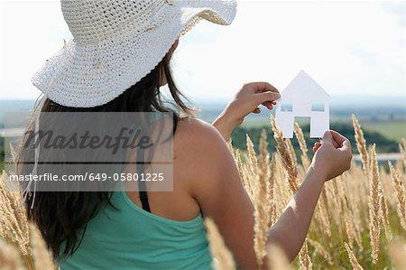 Femme tenant maison de papier découpé