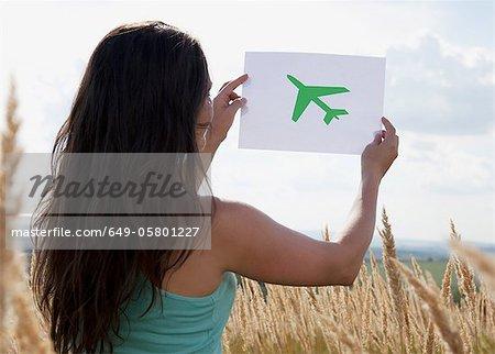 Femme tenant la photo de l'avion dans le ciel