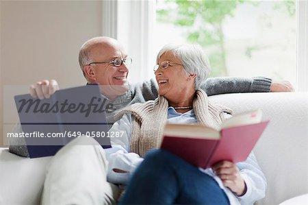Sourire vieux couple, lire des livres