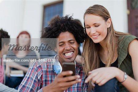 Étudiants sur le campus à l'aide de téléphone portable