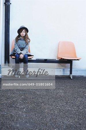 Fille assise sur une chaise à l'extérieur