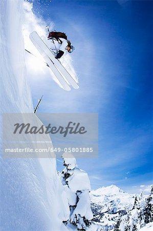 Skieur sautant sur une pente enneigée