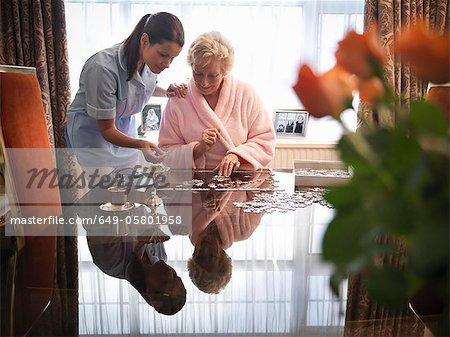 Krankenschwester und ältere Frau mit puzzle
