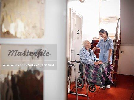 Nurse talking to older man in wheelchair