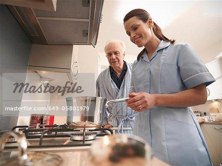Nurse cooking for older man in kitchen