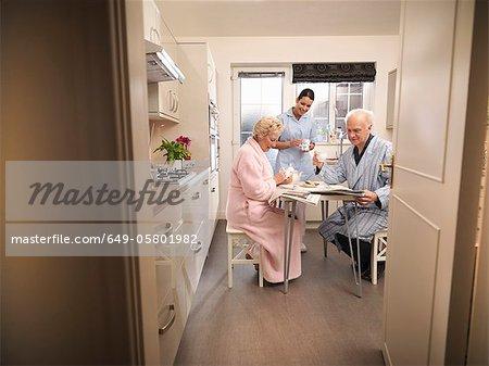 Nurse bringing older couple coffee
