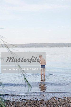 Junge waten auf felsigen Strand