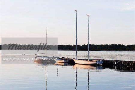 Yachts amarrés au quai au coucher du soleil